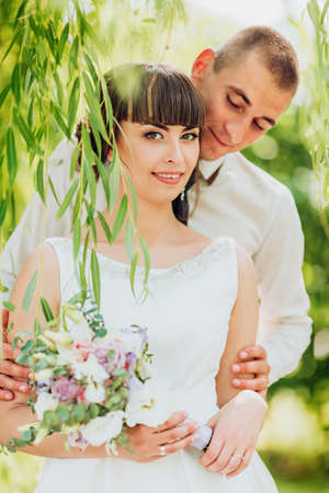 Bride and Groom at wedding Day walking Outdoors on spring nature. Bridal couple, Happy Newlywed woman and man embracing in green park. Loving wedding couple outdoor. Banco de Imagens