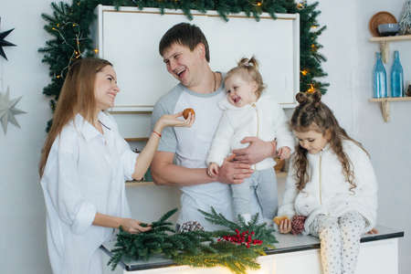 Happy little girls with mom and dad among the New Year's scenery Reklamní fotografie