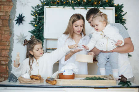 Big happy family baking with little daughters on a kitchen Banco de Imagens