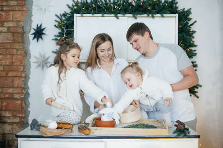 Big happy family baking with little daughters on a kitchen Archivio Fotografico - 100773442