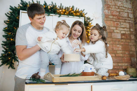 Big happy family baking with little daughters on a kitchen Archivio Fotografico - 100773446