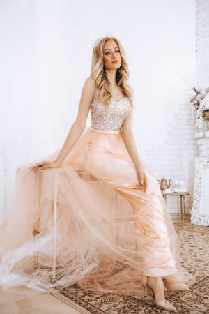 Portrait of beautiful blonde woman with makeup in fashion clothes and crown