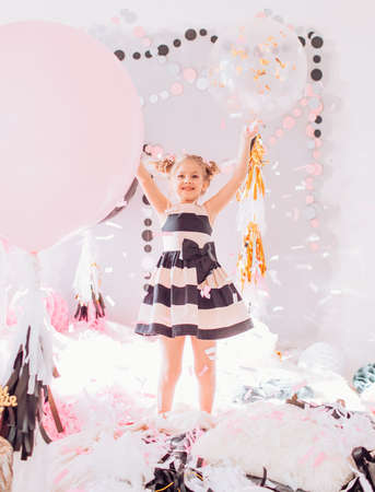 Beautiful little girl celebrating birthday party with big bouncy balls. Family celebration of the child Stock Photo