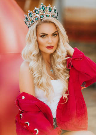 Portrait of beautiful blonde woman with makeup in fashion bright clothes and crown
