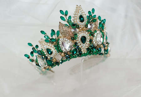 Beautiful green crown on a gray background for the design