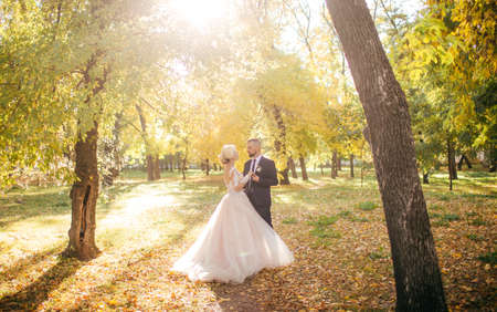 Bride and Groom at Wedding Day walking Outdoors on autumn nature. Bridal couple, Happy Newlywed woman and man embracing in autumn park. Loving wedding couple outdoor. Фото со стока