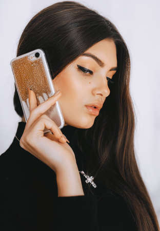 Portrait of beautiful young brunette with a mobile telephone