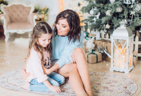 Happy girl with mother near Christmas tree