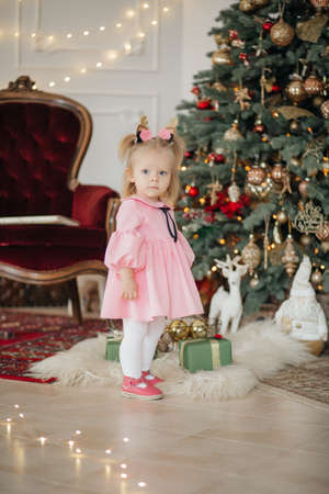 Beautiful baby girl near a Christmas tree