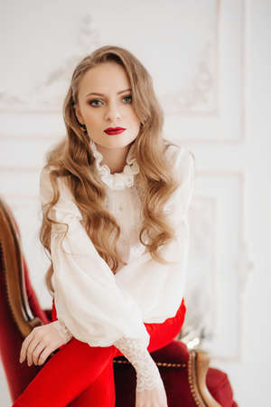 Portrait of beautiful young blonde woman with makeup in fashion clothes