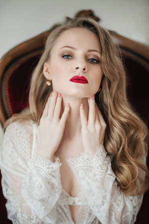 Portrait of beautiful young blonde woman with makeup in fashion white clothes