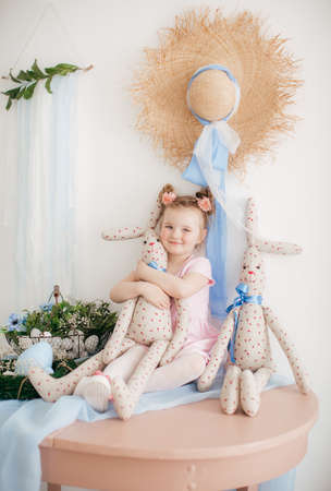 Cute little girl with a bunny rabbit at Easter.