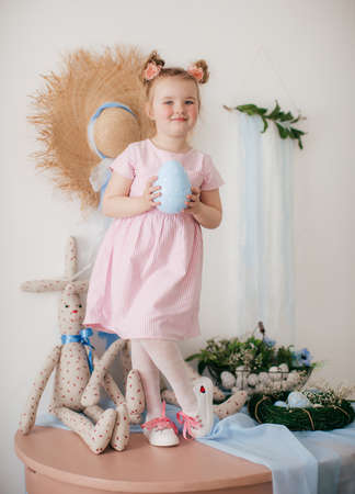 Cute little girl with a bunny rabbit at Easter. Stock Photo - 137422078