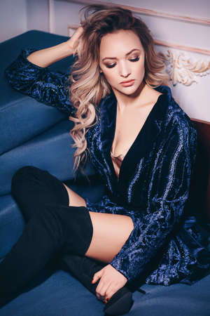 Portrait of beautiful young blonde woman with makeup in fashion blue clothes Imagens