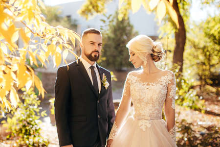 Happy bride and groom on their wedding in autumn garden Archivio Fotografico