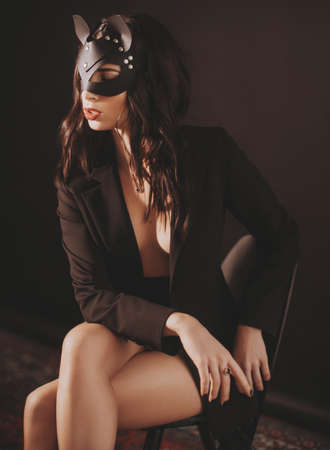 Portrait of beautiful young girl with makeup in black fashion clothes and mask
