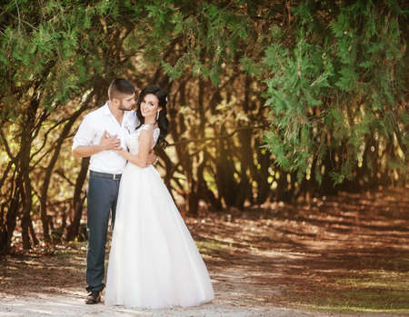 Bride and Groom at wedding Day walking Outdoors on spring nature. Bridal couple, Happy Newlywed woman and man embracing in green park. Loving wedding couple outdoor. Stock Photo