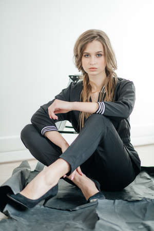 Portrait of a beautiful young girl with makeup in fashion clothes