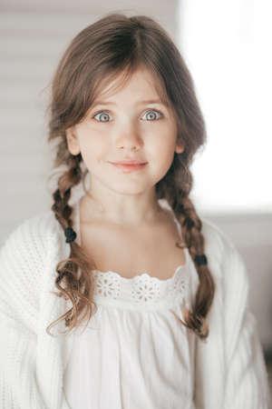 Porträt des schönen kleinen Mädchens mit Zöpfen