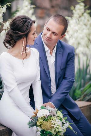 Braut und Bräutigam am Hochzeitstag, der draußen auf Frühlingsnatur geht. Brautpaar, glückliche frisch verheiratete Frau und Mann, die im grünen Park umarmen. Liebevolles Hochzeitspaar im Freien.