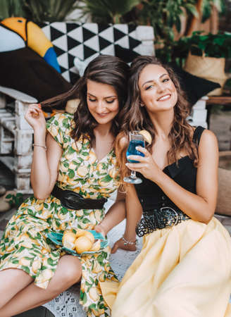 Portrait of two beautiful young women in a summer arbor with fruits