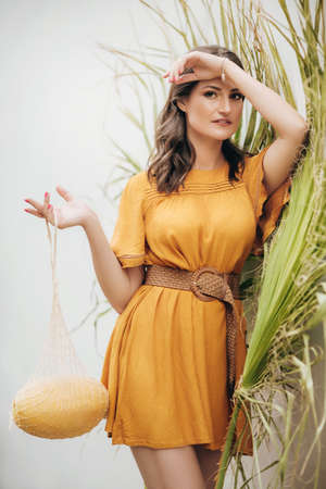 Beautiful young woman in orange dress with melon
