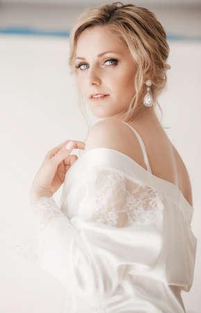 Hermosa novia rubia con maquillaje elegante en vestido blanco Foto de archivo