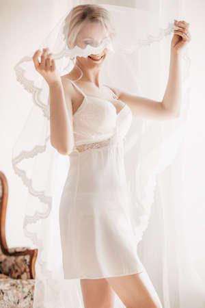 Schöne blonde Braut mit stilvollem Make-up im weißen Kleid. Morgenbraut Standard-Bild