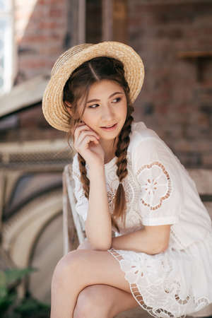 Portrait of beautiful girl with makeup with braids in yellow hat