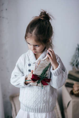 Stock Photo - Beautiful little girl with wooden christmas decor