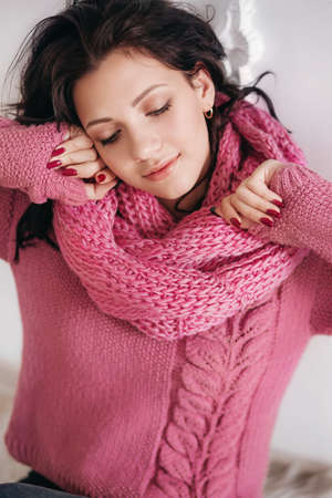 Portrait of beautiful young brunette woman with makeup in pink sweater