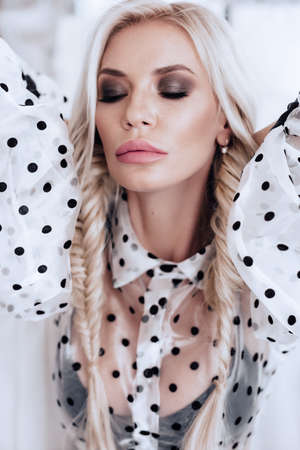 Portrait of beautiful young blonde woman with makeup in fashion white black clothes