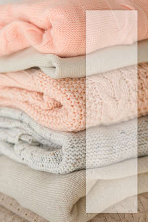 Stock Photo - Stack of cozy knitted sweaters with blank business card. For design presentations and portfolios.
