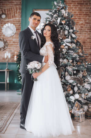 Happy bride and groom on their wedding in Christmas decorations with gifts Bridal couple, Happy Newlywed woman and man. Loving wedding couple. 版權商用圖片