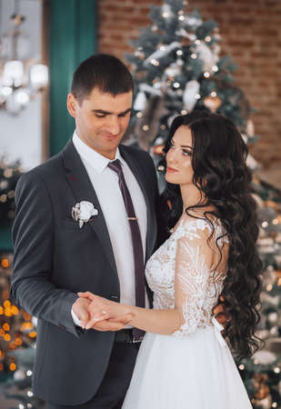 Happy bride and groom on their wedding in Christmas decorations with gifts Bridal couple, Happy Newlywed woman and man. Loving wedding couple. Imagens