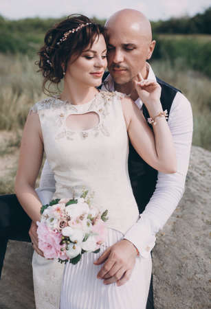 Bride and Groom at wedding Day walking Outdoors on spring nature. Bridal couple, Happy Newlywed woman and man embracing in green park. Loving wedding couple outdoor. 版權商用圖片