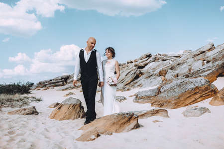 Bride and Groom at wedding Day walking Outdoors on spring nature. Bridal couple, Happy Newlywed woman and man. Loving wedding couple outdoor.