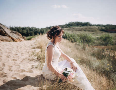 Beautiful bride in white dress on nature
