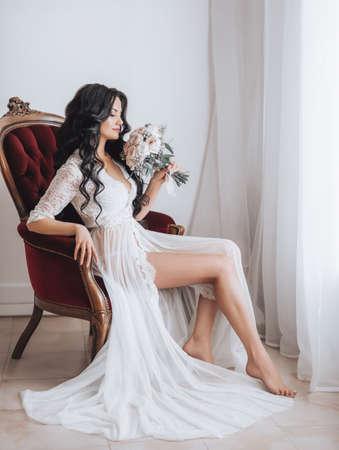Beautiful brunette bride with stylish make-up in white underwear.Morning bride