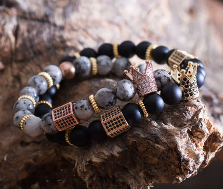 Stock Photo - bracelet with little crown on stone texture