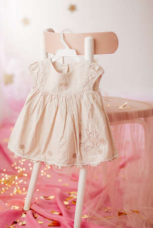 Stock Photo - Child dress on hanger on pink background