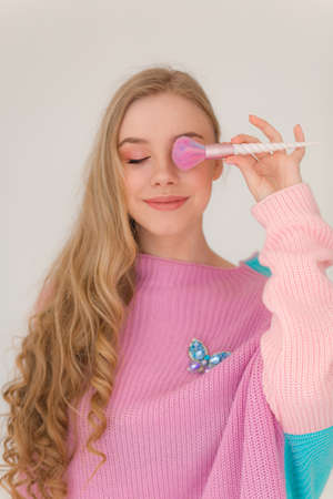 Photo of beautiful young girl with makeup brush in a colorful clothes