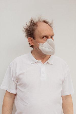 Stock Photo - Senior man in a white t-shirt wearing medical mask Imagens