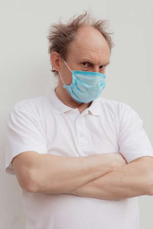 Stock Photo - Senior man in a white t-shirt wearing medical mask