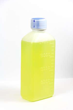 Green mixture in white plastic bottle