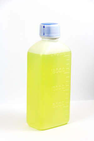 Green mixture in white plastic bottle