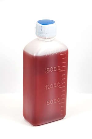 Brown mixture in white plastic bottle