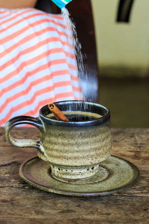 Add sugar to a cup of coffee