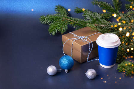 Blank blue takeaway coffee cup with Christmas decorations and golden gift box near pine tree branches. Stock fotó