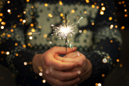 Man in sweater with deers holding bright festive Christmas sparkler in hand.